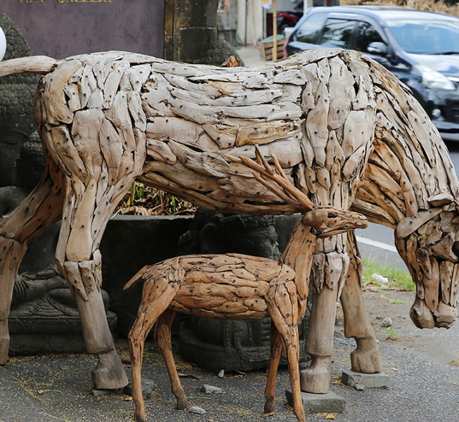Big Cow and small deer from teak root. Handicraft and art from Bali