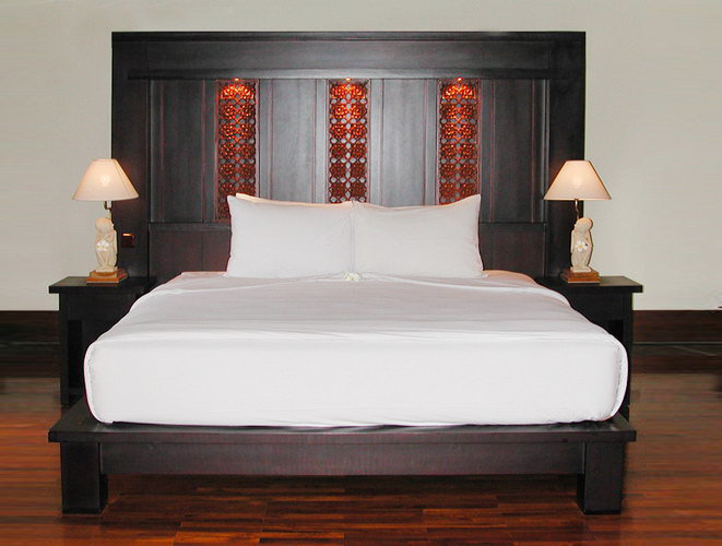 teak bed with sculpted high headboard matching bedside andlamp with stone statue