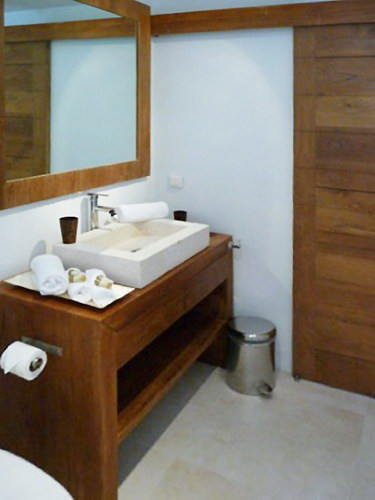 bathroom teak furniture with marble sinks anbd huge mirror