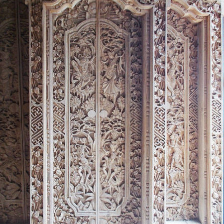Old balinese temple double door in white wood with carvings