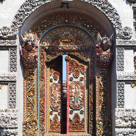 Old Balinese temple double door in teak wood with carvings and gold decoration with 2 wood singha on the front
