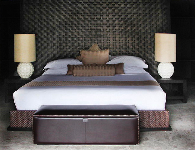 rattan weaved bed with headboard and a leather box