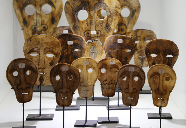 Primitive art and decoration from Indonesia. Carved bone masks on stand.