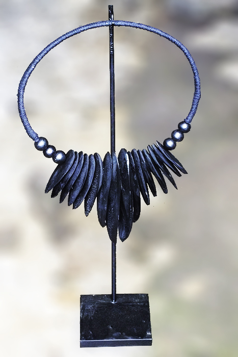 Papua cuttlefish necklace on stand. Primitive art and decoration from Indonesia.