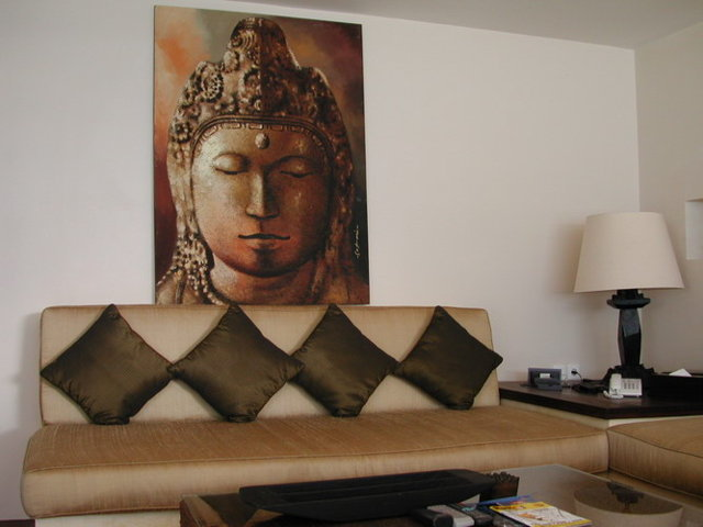 Buddha painting in the back and some a well decorated couch
