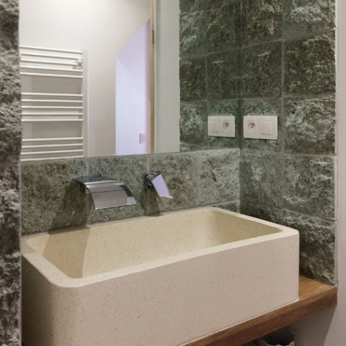 green stone covered walls with a terrazzo ressin sink from the side