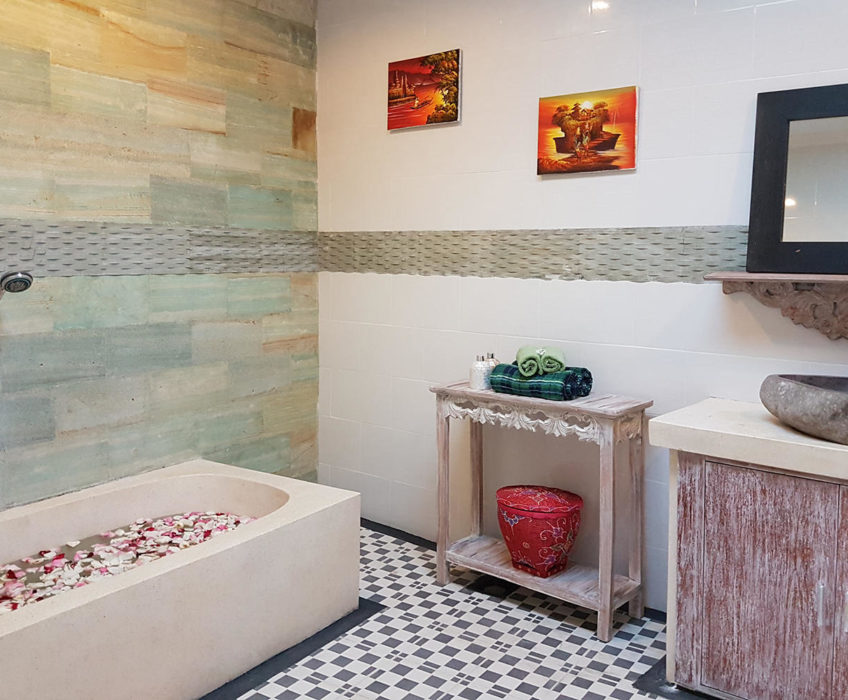 Teak furniture in the bathroom and a bathtub. Decorate with paintings on the wall