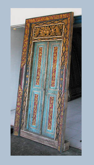 Old Balinese temple double door in teak wood with carvings and gold decoration and painting