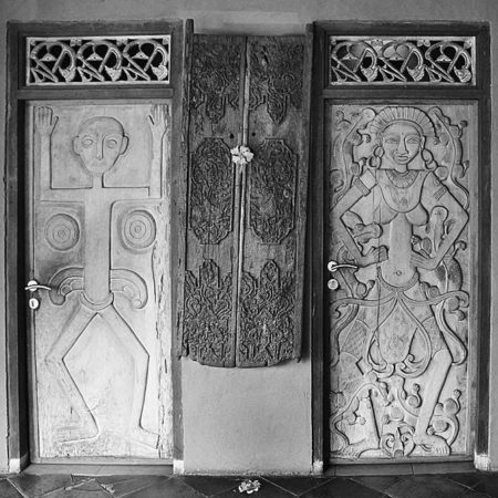 Primitive light wood door with carved statue tumor or balinese dancer woman Bayu International Trading Bali Indonesia