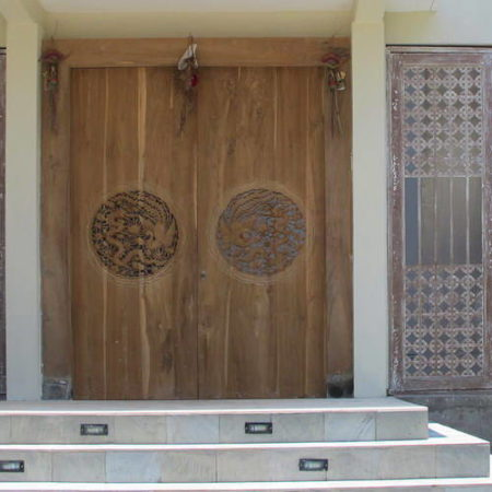 Entry door made from teak wood decorated with Chinese carvings Bayu International Trading Bali Indonesia