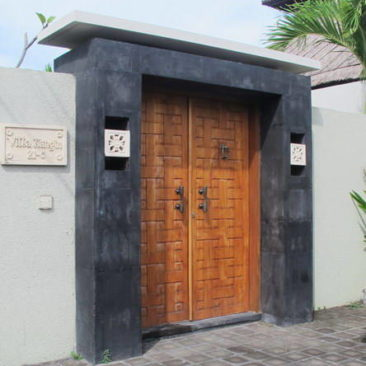Teak wood door for entry to villa with geometric carving panel and heavy brass Bayu International Trading Bali Indonesia